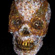 Skull covered in Crushed stones and gold braid -$75